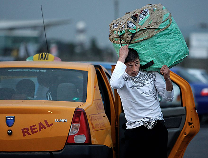 "A Romanian Roma man holds a large bag next to a taxi after he and more than 200 others arrived on two special flights from France, in Bucharest, Romania, Tuesday, Sept. 14, 2010. France's deportations of Gypsies are ""a disgrace"" and probably break EU law, the European Union's executive body declared Tuesday in a stinging rebuke that set up a showdown with French President Nicolas Sarkozy's conservative government. (AP Photo/Vadim Ghirda)"
