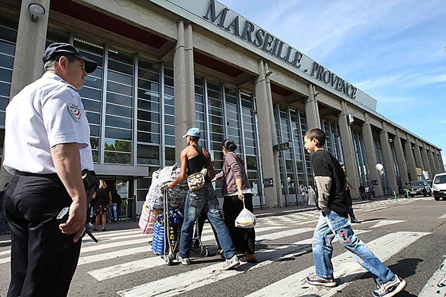 """Roma also known as Gypsies, arrive at Marseille airport, southern France, before being expelled from France, Tuesday, Sept. 14, 2010. France's deportations of Gypsies are """"a disgrace"""" and probably break EU law, the European Union's executive body declared Tuesday, setting up a showdown with the government of French President Nicolas Sarkozy. In recent weeks, French authorities have dismantled over 100 illegal camps and deported more than 1,000 Roma, mainly back to Romania, in a crackdown that has drawn international condemnation. (AP Photo/Claude Paris)"""
