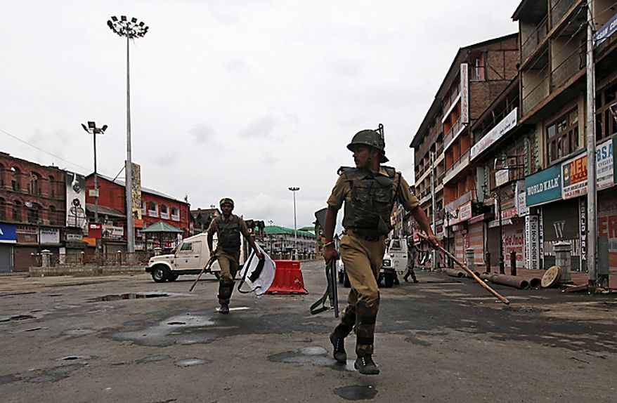 Indian paramilitary soliders run to take positions as they are deployed  during curfew in Srinagar, India, Tuesday, Sept.14, 2010. Indian police patrolled the streets of Kashmir on Tuesday, threatening to shoot anyone defying a rigid curfew imposed on the region a day after troops battled protesters in the streets in violence that killed several people. (AP Photo/Dar Yasin)