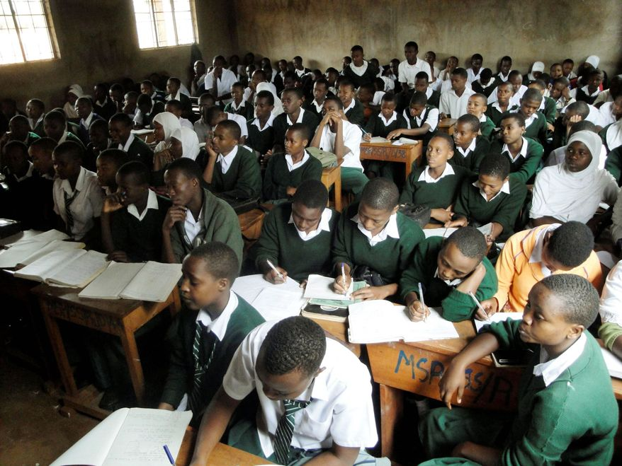 Students crowd a biology class at Msaranga Secondary School near Moshi, Tanzania, where youngsters hunger for education. To get into the classroom, however, they have to pay substantial fees for items such as uniforms and desks. (Associated Press)