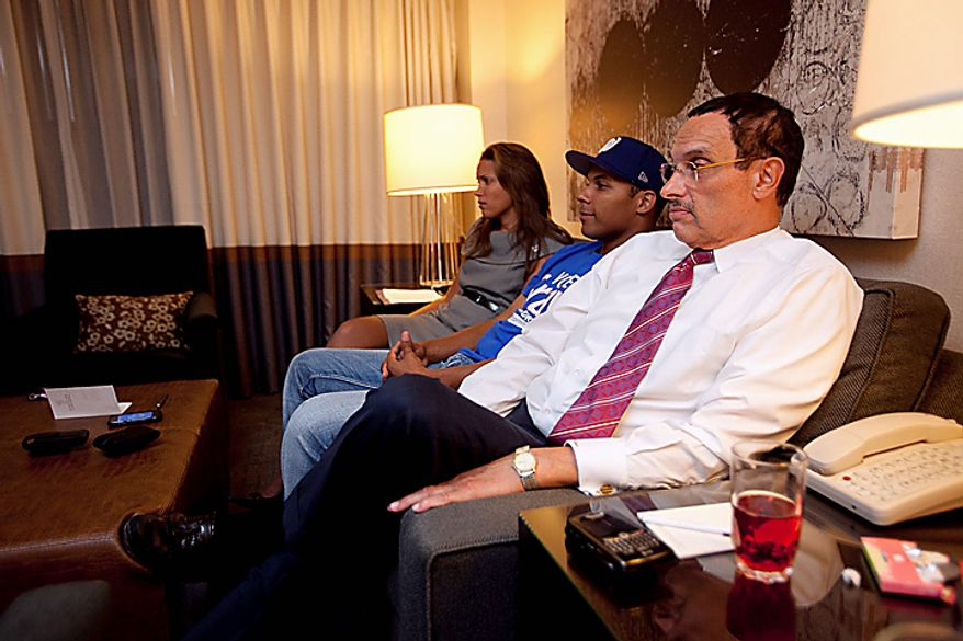 Democratic Mayoral Candidate Vincent Gray watches the television from a hotel room as voting numbers come in late Tuesday night, Sept. 14, 2010, with his daughter  Jonice Gray Tucker and son Carlos Gray in Washington. (AP Photo/Examiner, Andrew Harnik, Pool)