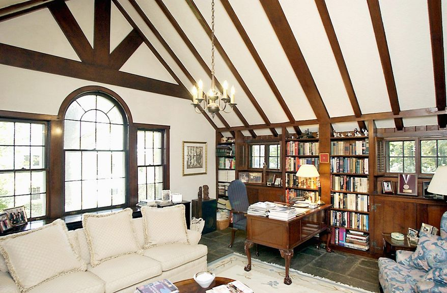 The library has a wood-beamed cathedral ceiling and a Palladian window that overlooks the garden. Built-in mahogany shelves, cabinets and paneling line the room.