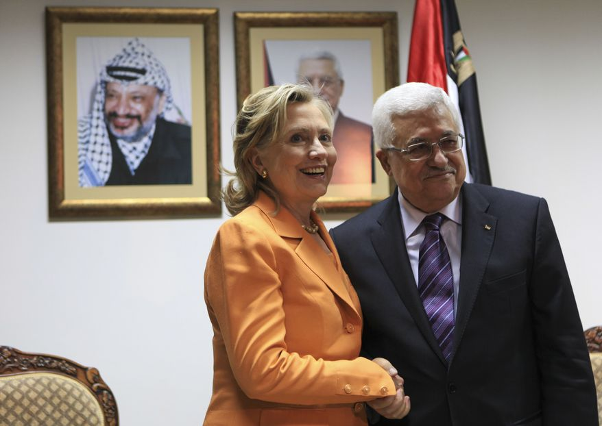 Secretary of State Hillary Rodham Clinton and Palestinian President Mahmoud Abbas shake hands during their meeting in the West Bank city of Ramallah on Thursday, Sept. 16, 2010. After two days of inconclusive Mideast peace negotiations, Mrs. Clinton traveled Thursday to the Palestinian Authority's headquarters in the West Bank to confer with Mr. Abbas. On the wall are portraits of the late Palestinian leader Yasser Arafat (left) and Mr. Abbas. (AP Photo/Fadi Arouri, Pool)