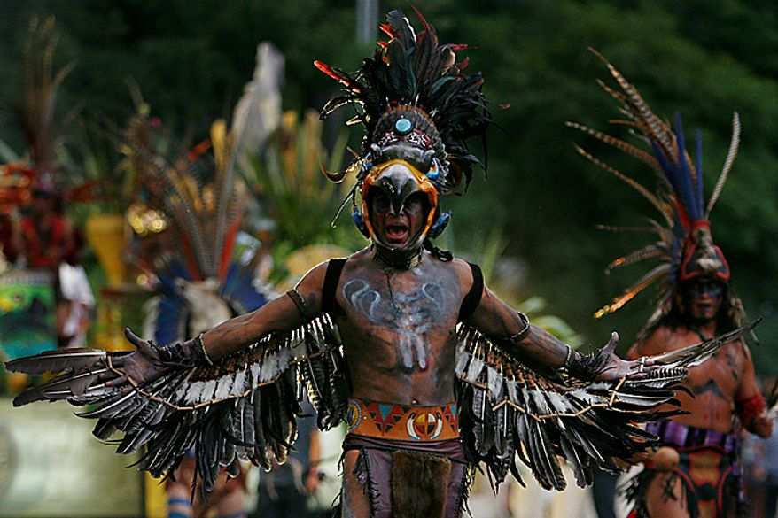 Men wearing Aztec costumes perform during the bicentennial parade in Mexico City, Wednesday Sept. 15, 2010.  Mexico celebrates the 200th anniversary of its 1810 independence uprising. (AP Photo/Miguel Tovar)