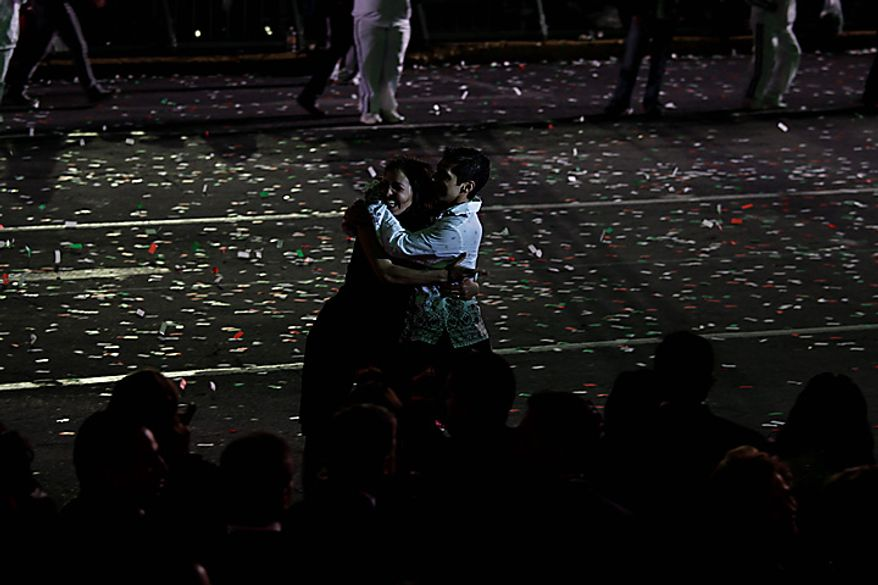 Performers embrace during bicentennial celebrations in Mexico City's main Zocalo plaza, Wednesday Sept. 15, 2010. Mexico celebrates the 200th anniversary of its 1810 independence uprising. (AP Photo/Dario Lopez-Mills)