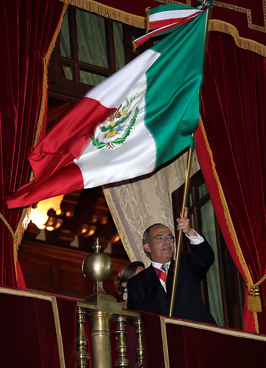 Mexico's President Felipe Calderon waves the national flag from the balcony of National Palace during bicentennial celebrations in Mexico City's main Zocalo plaza, Wednesday Sept. 15, 2010. Mexico celebrates the 200th anniversary of its 1810 independence uprising. (AP Photo/Dario Lopez-Mills)