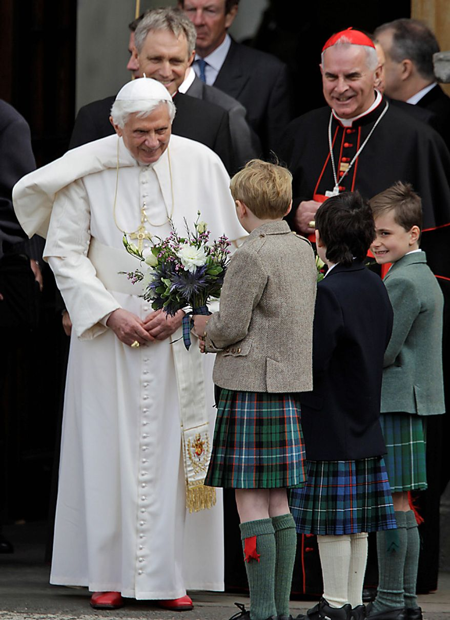 Pope Benedict XVI receives flowers from youths while leaving the Palace of Holyroodhouse, in Edinburgh, Scotland, Thursday Sept. 16, 2010. (AP Photo/Lefteris Pitarakis, pool)