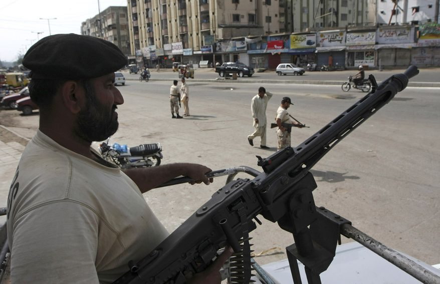 Soldiers of Pakistan's paramilitary forces stand guard on the roadside as tension mounted after killing of Pakistani local leader Imran Farooq in London, on Friday, Sept. 178, 2010 in Karachi, Pakistan. Gangs torched vehicles and a shop in Karachi on Friday after Farooq was stabbed to death in London. (AP Photo/Fareed Khan)