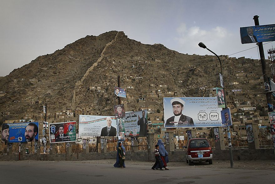 Afghans walk past under election posters of parliamentarian candidates on the eve of the parliamentary election in Kabul, Afghanistan, Friday, Sept. 17, 2010. Afghanistan will go to parliamentary election on Sept. 18 as the Taliban have warned of countrywide attacks on Saturday targeting voters and election workers. (AP Photo/Musadeq Sadeq)
