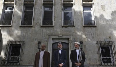 Afghan President Hamid Karzai, center, flanked by First Vice President Muhammad Qasim Fahim, left, and Second Vice President Mohammad Karim Khalili delivers a speech in Kabul, Afghanistan, Friday, Sept. 17, 2010. Karzai urged Afghans to vote in this weekend's parliamentary election despite threats from the Taliban warning people not to leave their homes. (AP Photo/ Gemunu Amarasinghe)
