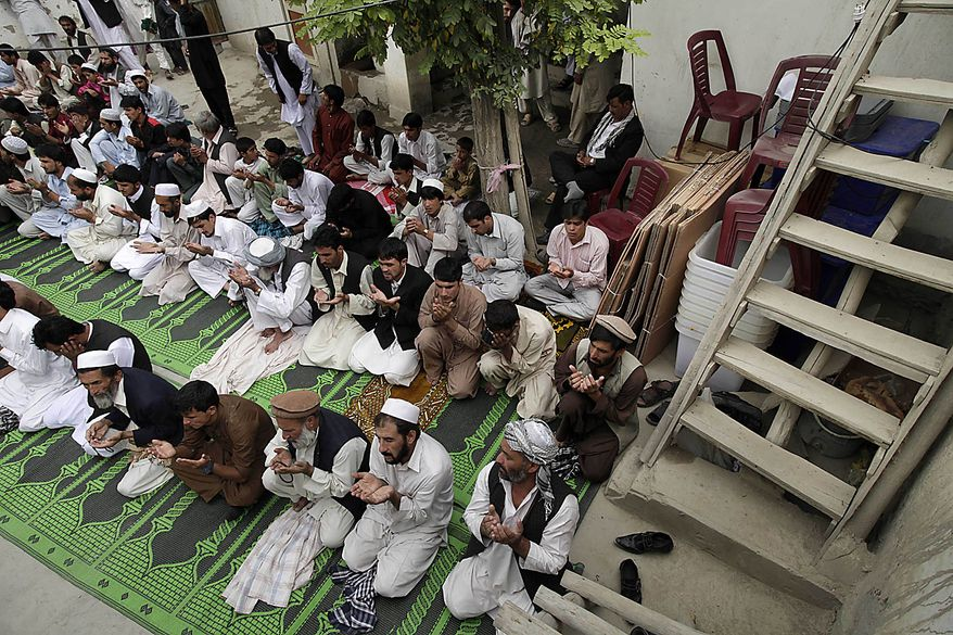 Polling materials are stashed in a corner as people pray at a mosque that will serve as a polling station in Kabul, Afghanistan, Friday, Sept. 17, 2010. Afghanistan will elect the lower house of its parliament on Saturday. (AP Photo/Saurabh Das)