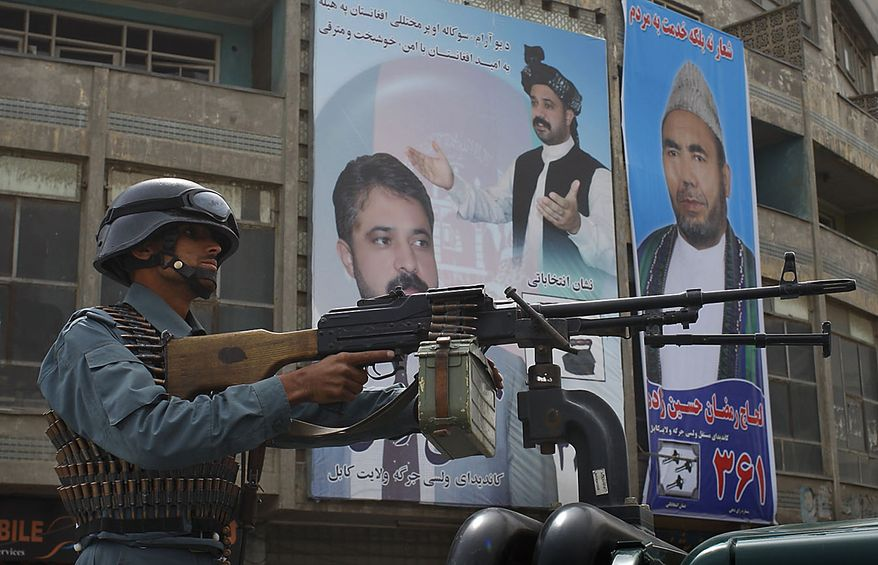 A police officer mans a machine gun on a street corner a day ahead of parliamentary elections in Kabul, Afghanistan, Friday, Sept. 17, 2010. Afghanistan will elect the lower house of its parliament on Saturday. (AP Photo/Saurabh Das)