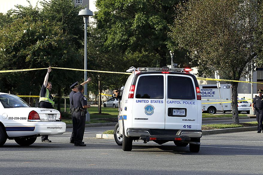 Police officers at the scene of a shooting on Capitol Hill in Washington on Friday, Sept. 17,  2010. Authorities in Washington say police shot a man who pointed a gun at them on Capitol Hill. (AP Photo/Jose Luis Magana)