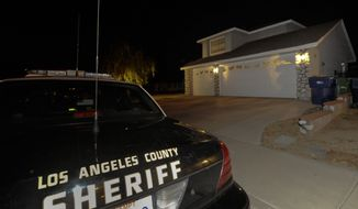"Los Angeles County sheriff's officers sit outside the home of Reyna Marisol Chicas, the leader of a ""cultlike"" group who has been reported missing along with 12 other members on Saturday, Sept. 18, 2010, in Palmdale, Calif. (AP Photo/Gus Ruelas)"