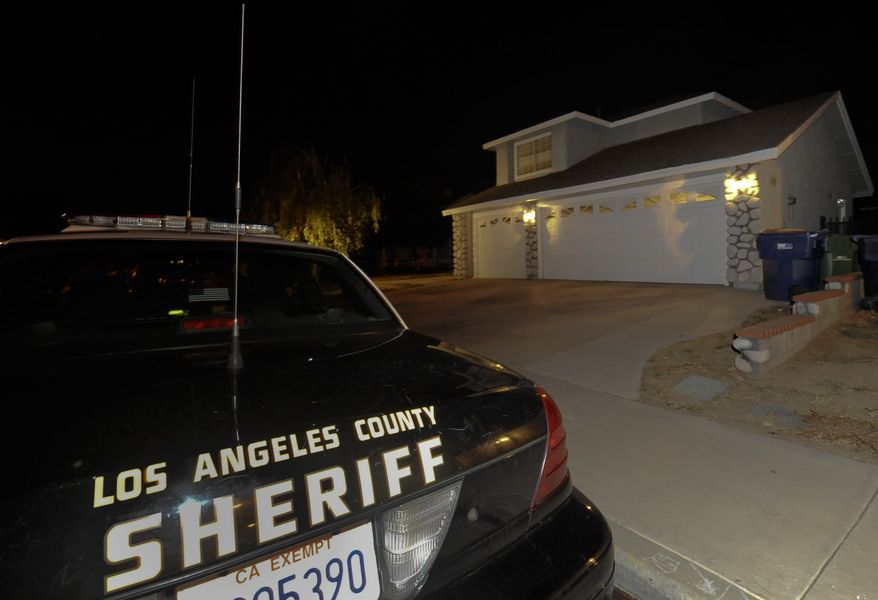 """Los Angeles County sheriff's officers sit outside the home of Reyna Marisol Chicas, the leader of a """"cultlike"""" group who has been reported missing along with 12 other members on Saturday, Sept. 18, 2010, in Palmdale, Calif. (AP Photo/Gus Ruelas)"""