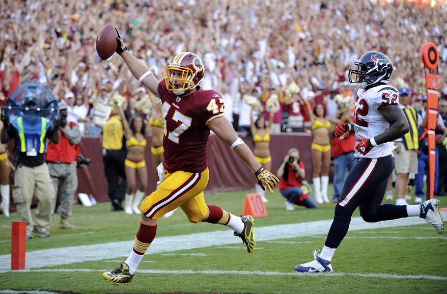 ASSOCIATED PRESS Washington Redskins tight end Chris Cooley scores a touchdown as Houston Texans linebacker Xavier Adibi watches during the second half an NFL football game in Landover, Md., on Sunday, Sept. 19, 2010.