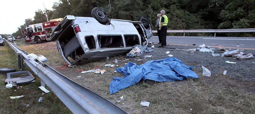 State police investigate a fatal accident on Saturday, Sept. 18, 2010, in Woodbury, N.Y., in which a passenger van carrying members of a church flipped over on the New York State Thruway. The bishop of the small church and five other members died in the crash, and eight others were injured. (AP Photo/Times Herald-Record, Michele Haskell)