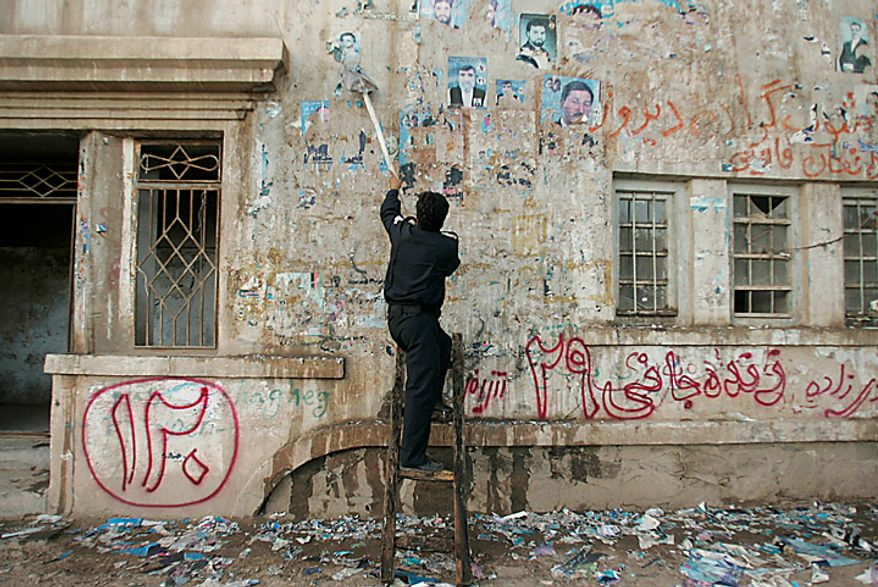 A policeman scrapes a wall clean of posters of candidates who contested in the parliamentary elections, in Herat, Afghanistan, Monday Sept. 20, 2010. Afghan election observers urged President Hamid Karzai's government on Monday to allow an independent investigation into reports of widespread fraud during last weekend's parliamentary elections, including intimidation of voters and interference by powerful warlords. (AP Photo/ Reza Shirmohammadi)
