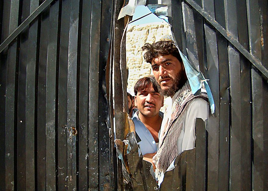 Local villagers look through a damaged gate of a house that was allegedly raided by international security forces at Matun district of Khost province in Afghanistan, Monday, Sept. 20, 2010. One person was allegedly killed and two were taken away after the operation. (AP Photo/Nishanuddin Khan)