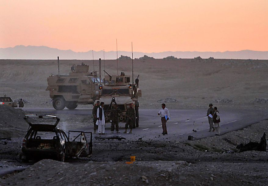U.S soldiers inspect a site after a suicide car-bomb in Behsood district of Jalalabad, Afghanistan, Monday Sept. 20, 2010. The attack on a NATO convoy reportedly injured four Afghan civilians. (AP Photo/Rahmat Gul)