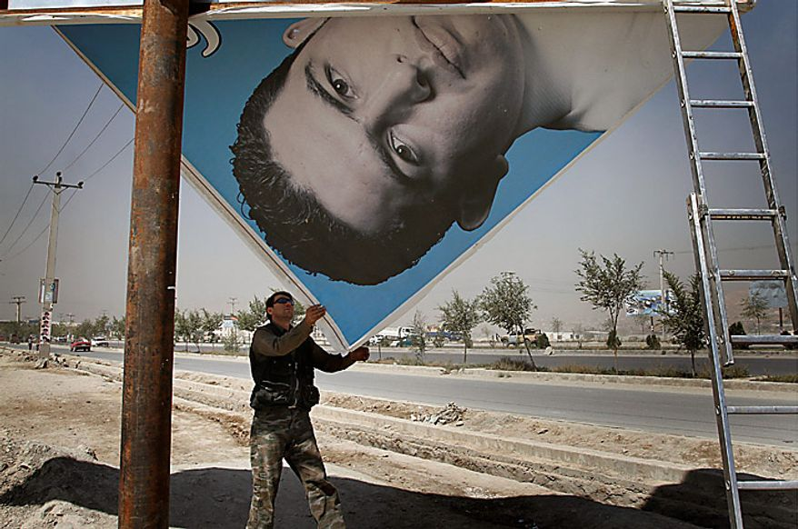 A worker dismantles a poster of election candidate two days after parliamentary election in Kabul, Afghanistan, Monday, Sept. 20, 2010. The main Afghan election observer group said it had serious concerns about the legitimacy of this weekend's parliamentary vote because of reported fraud, even as President Hamid Karzai commended the balloting as a solid success. (AP Photo/Musadeq Sadeq)