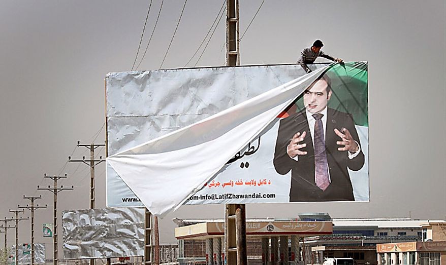 A worker dismantles a poster of an election candidate in Kabul, Afghanistan, Monday, Sept. 20, 2010, two days after parliamentary election. The main Afghan election observer group said it had serious concerns about the legitimacy of this weekend's parliamentary vote because of reported fraud, even as President Hamid Karzai commended the balloting as a solid success. (AP Photo/Musadeq Sadeq)