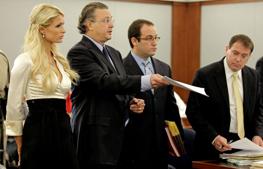 Paris Hilton, left, listens as her attorney David Chesnoff, center, shows the plea agreement to Judge Joe Bonaventure as prosecutor David Schubert, right looks on in county court Monday, Sept. 20, 2010, in Las Vegas. Hilton pleaded guilty to reduced charges in her August cocaine arrest. Under the terms of a plea deal worked out with prosecutors, the heiress will serve a year of probation and avoid a felony conviction. (AP Photo/Julie Jacobson)