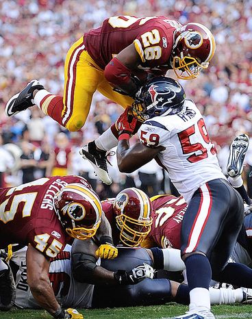 Washington Redskins running back Clinton Portis is stopped short of the goal line by Houston Texans linebacker DeMeco Ryans during the first half of an NFL football game in Landover, Md., on Sunday, Sept.. 19, 2010.  Portis scored on the next play. (AP Photo/Nick Wass)