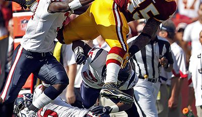 Washington Redskins running back Mike Sellers leaps over Houston Texans safety Bernard Pollard (31), safety Eugene Wilson (26) and defensive back Kareem Jackson (25) during the first half of an NFL football game in Landover, Md., on Sunday, Sept.. 19, 2010.  (AP Photo/Evan Vucci)
