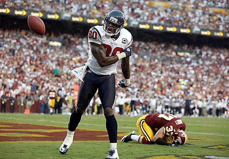 Houston Texans wide receiver Andre Johnson celebrates a touchdown as Washington Redskins safety Reed Doughty reacts in the background during the second half an NFL football game in Landover, Md., on Sunday, Sept. 19, 2010.  (AP Photo/Evan Vucci)