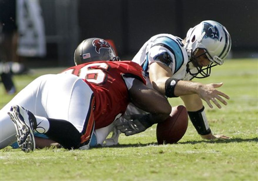 Carolina Panthers' Matt Moore (3) throws a pass under pressure from Tampa Bay Buccaneers' Stylez White (91) in the first quarter of an NFL football game in Charlotte, N.C., Sunday, Sept. 19, 2010. (AP Photo/Chuck Burton)