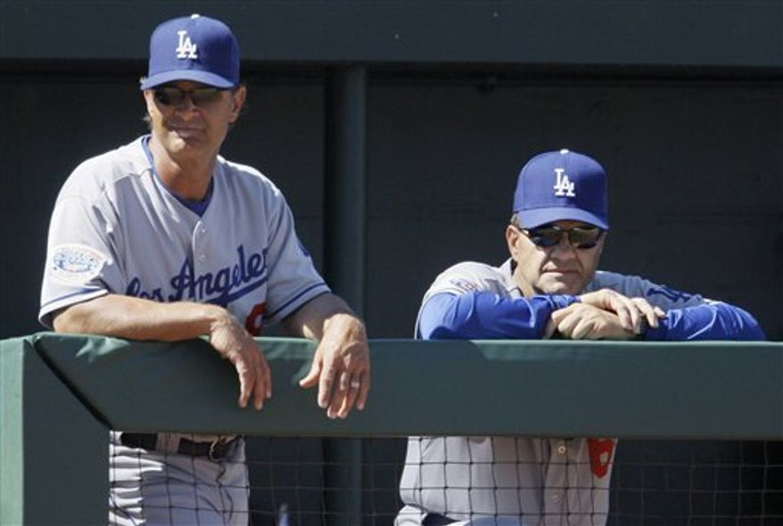 FILE - In this March 15, 2010, file photo, Los Angeles Dodgers' manager Joe Torre, right, and hitting coach Don Mattingly watch from the dugout rail as the Dodgers play the Los Angeles Angels in the third inning of a spring training baseball game in Tempe, Ariz.  A Dodgers official speaking on condition of anonymity tell The Associated Press that Joe Torre intends to retire as Los Angeles Dodgers manager at the end of the season and will be replaced by hitting coach Don Mattingly. (AP Photo/Jeff Chiu, File)