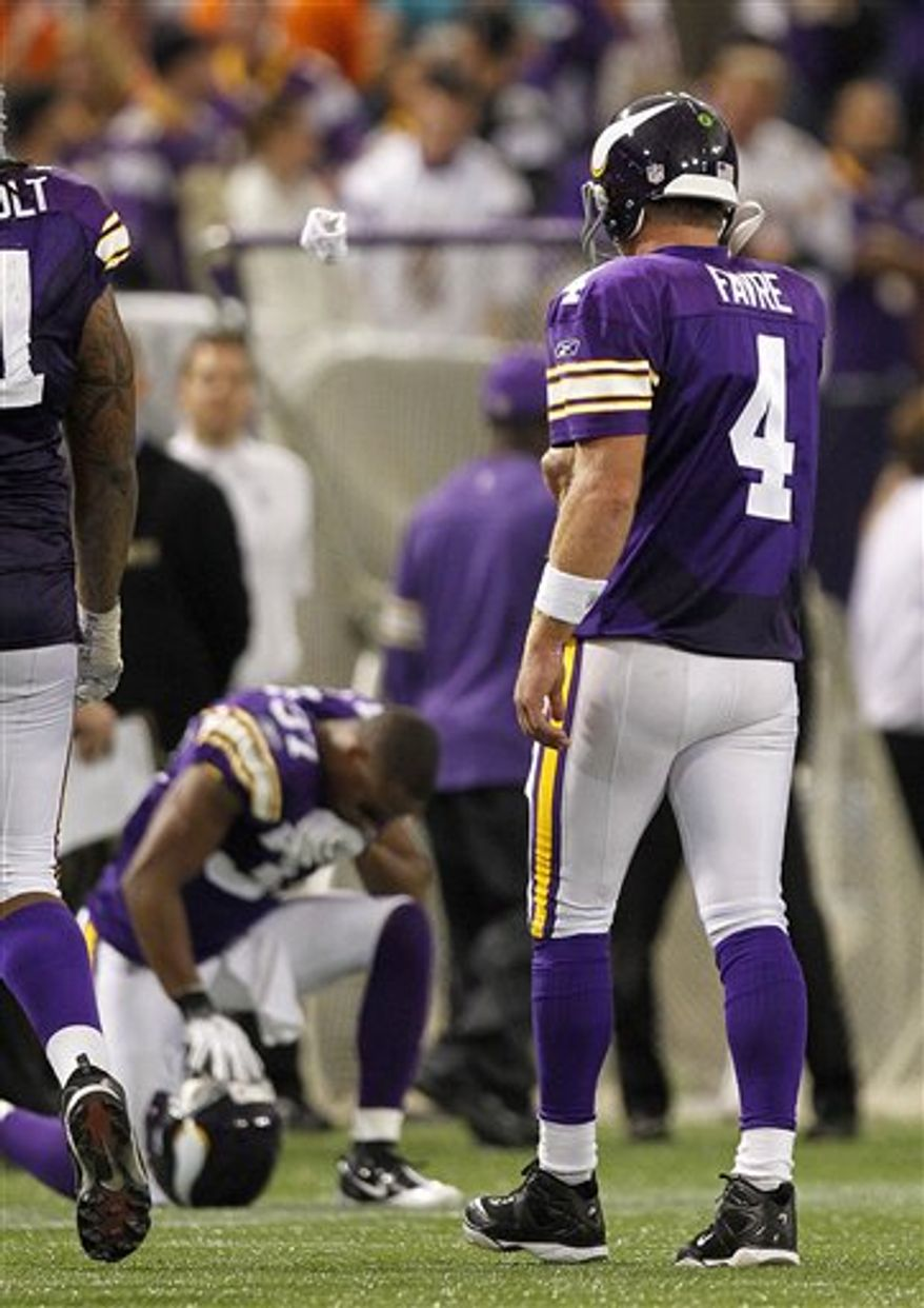 Minnesota Vikings quarterback walks off the field after the Vikings drive stalled against the Miami Dolphins in the fourth quarter with Vikings Eric Frampton kneeling during their NFL football game in Minneapolis Sunday, Sept. 19, 2010. The Dolphins beat the Vikings 14-10.(AP Photo/Andy King)