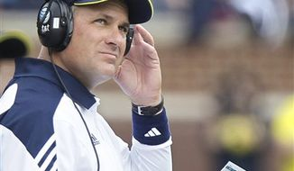 Michigan head football coach Rich Rodriguez watches from the sidelines during the second quarter of a college football game against Massachusetts in Ann Arbor, Mich., Saturday, Sept. 18, 2010. (AP Photo/Carlos Osorio)