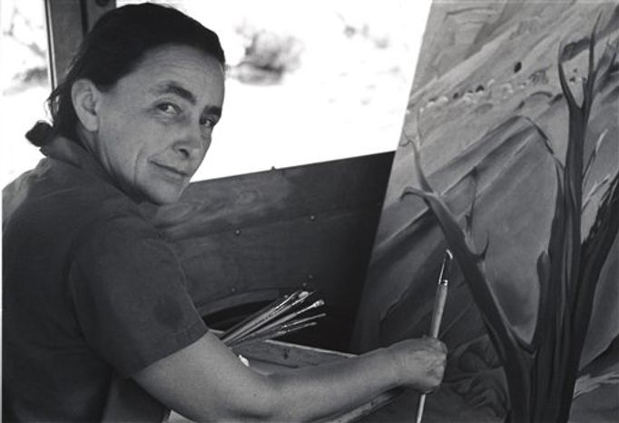 "This 1960 image provided by the Georgia O'Keeffe Museum, Tony Vaccaro, shows American modernist painter Georgia O'Keeffe looking through a piece of cheese. A new exhibition, ""O'Keeffiana: Art and Art Materials,"" opens at the Georgia O'Keeffe Museum in Santa Fe, N.M., on Sept. 24, 2010. It includes O'Keeffe&amp"