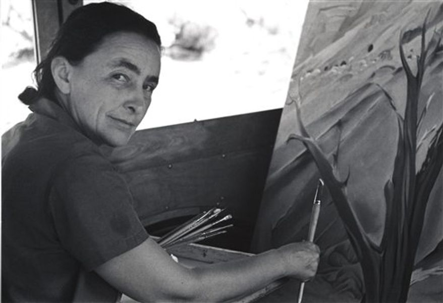 """This 1960 image provided by the Georgia O'Keeffe Museum, Tony Vaccaro, shows American modernist painter Georgia O'Keeffe looking through a piece of cheese. A new exhibition, """"O'Keeffiana: Art and Art Materials,"""" opens at the Georgia O'Keeffe Museum in Santa Fe, N.M., on Sept. 24, 2010. It includes O'Keeffe's art supplies, drawings, unfinished paintings and the rocks and bleached animal bones she used as subjects. (AP Photo/Tony Vaccaro, courtesy of the Georgia O'Keeffe Museum)  NO SALES"""