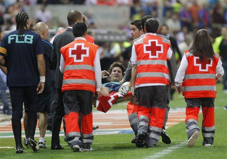 FC Barcelona's Lionel Messi from Argentina reacts after he was injured during a Spanish La Liga soccer match against Atletico de Madrid at the Vicente Calderon stadium in Madrid, Spain, Sunday, Sept  19, 2010. (AP Photo/Andres Kudacki)