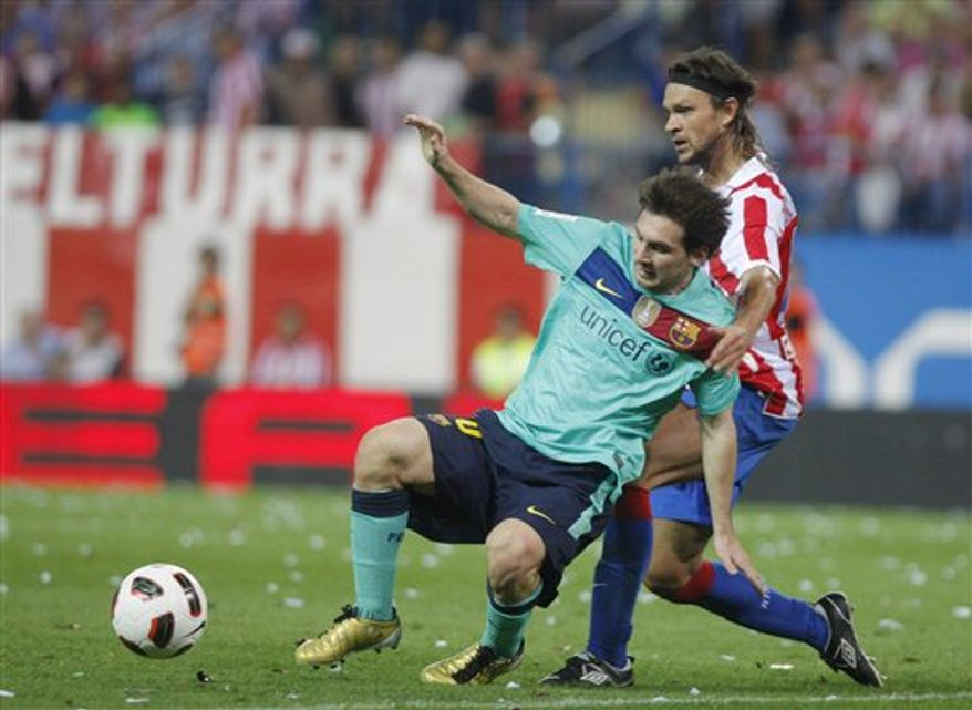 FC Barcelona's Lionel Messi from Argentina is tackled by Atletico de Madrid's Tomas Ujfalusi from Czech Republic during their Spanish La Liga soccer match at the Vicente Calderon stadium in Madrid, Spain, Sunday, September 19, 2010. (AP Photo/Andres Kudacki)