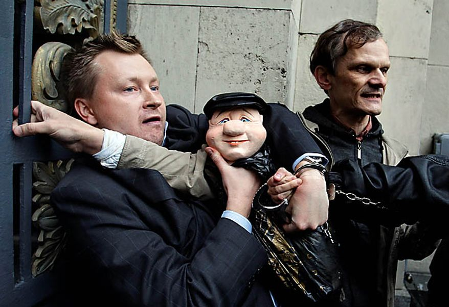 """Police officers detain a russian gay rights activist Nikolai Alexeyev holding a puppet of Moscow Mayor Yuri Luzhkov during a rally near city hall in Moscow, Tuesday, Sept., 21, 2010. Moscow police has dispersed a gay rally and detained activists protesting homophobic policies of Moscow authorities. Mayor Yuri Luzhkov has called homosexuals """"satanic"""" and routinely thwarted their attempts to hold a gay pride in Moscow. Police officers detained on Tuesday at least a dozen activists in a Moscow square near the city hall minutes after they brought out a papier-mache mummy that resembled Luzhkov and unfurled posters ridiculing him.  (AP Photo/Sergey Ponomarev)"""