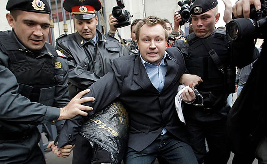 "Police officers detain Russian gay rights activist Nikolai Alexeyev during a rally near city hall in Moscow, Tuesday, Sept. 21, 2010. Moscow police has dispersed a gay rally and detained activists protesting homophobic policies of Moscow authorities. Mayor Yuri Luzhkov has called homosexuals ""satanic"" and routinely thwarted their attempts to hold a gay pride in Moscow. Police officers detained on Tuesday at least a dozen activists in a Moscow square near the city hall minutes after they brought out a papier-mache mummy that resembled Luzhkov and unfurled posters ridiculing him. (AP Photo/Sergey Ponomarev)"
