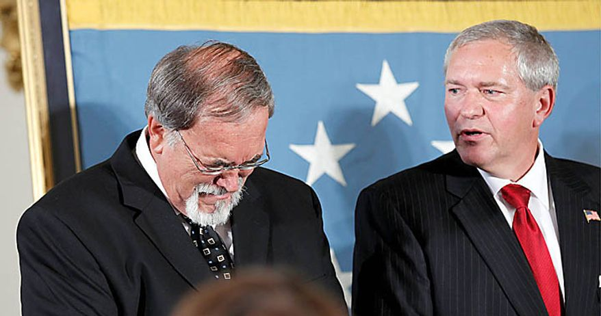 Steve Wilson, left, and Corey Etchberger, right, react as President Barack Obama presents the Medal of Honor posthumously to their father Air Force Chief Master Sgt. Richard L. Etchberger, Tuesday, Sept. 21, 2010, during a ceremony in the East Room of the White House in Washington. Etchberger received the honor for his heroic actions in combat in Laos on March 11, 1968, after deliberately exposing himself to enemy fire in order to put his wounded comrades in rescue slings permitting them to be airlifted to safety. (AP Photo/Pablo Martinez Monsivais)
