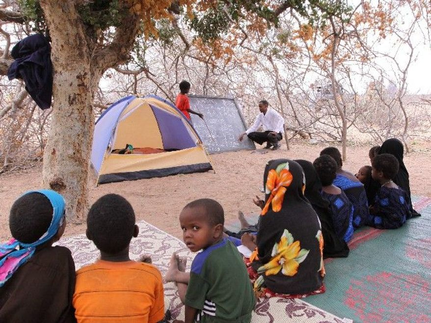 Children study in scant shade in Dertu, where school attendance has doubled for boys and tripled for girls. Their teacher lives in a backpacker's tent and will move with the nomads when they do. (Associated Press)