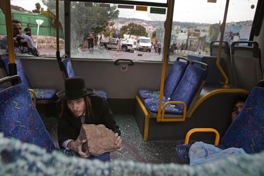Two ultra-Orthodox Jewish men protect themselves inside a bus from Palestinian rioters outside Jerusalem's Old City on Wednesday, Sept. 22, 2010. Violence erupted after a 32-year-old Palestinian laborer was killed by a private security guard watching over Jewish families in the Silwan neighborhood in east Jerusalem. During the man's funeral, a mob of protesters set tires on fire, smashed the windows of several buses and called for revenge. (AP Photo/Bernat Armangue)