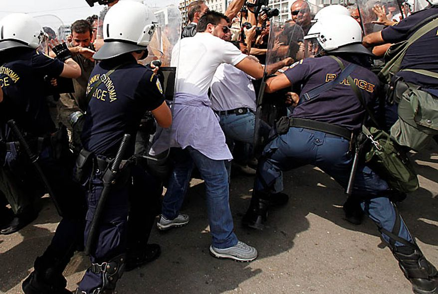 Truck drivers clash with riot police outside the Greek Parliament in Athens, Wednesday, Sept. 22, 2010. Truckers strongly oppose government plans to reform their sector and abolish strict licensing rules. (AP Photo/Dimitri Messinis)