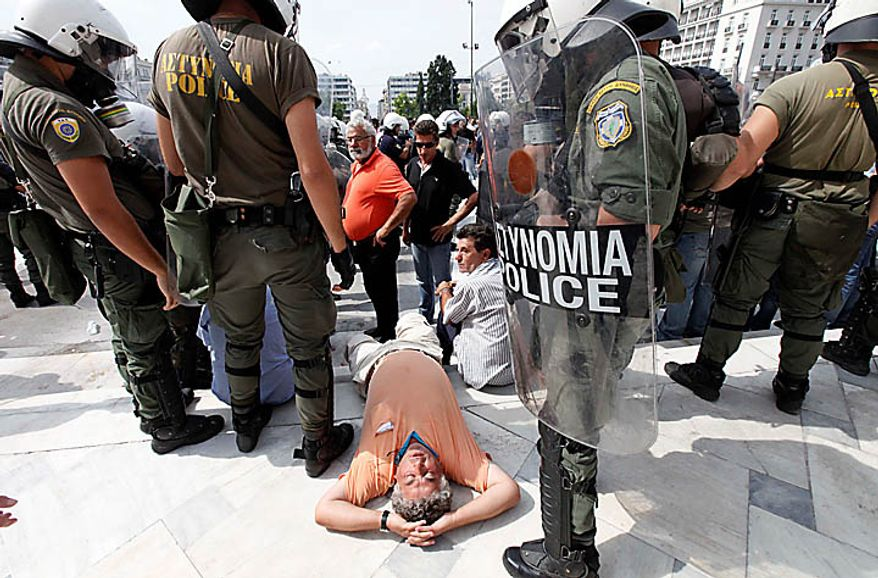 A truck lies down in protest in front of riot police offices during a demonstration outside the Greek Parliament in Athens, Wednesday, Sept. 22, 2010. Truckers strongly oppose government plans to reform their sector and abolish strict licensing rules. (AP Photo/Dimitri Messinis)