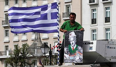 A truck driver holds a poster depicting  Greek Premier George Papandreou as legendary comic actor Charlie Chaplin, during a protest outside the Greek Parliament in Athens, Wednesday, Sept. 22, 2010. Truckers strongly oppose government plans to reform their sector and abolish strict licensing rules. (AP Photo/Alkis Konstantinidis)