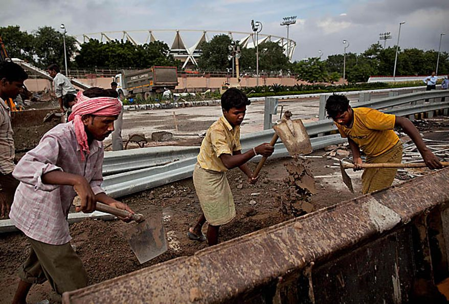 """Indian laborers work outside Jawaharlal  Nehru stadium, the main venue for the Commonwealth Games,in New Delhi, India, Wednesday, Sept. 22, 2010. The Commonwealth Games chief rushed to New Delhi seeking emergency talks with the prime minister over India's chaotic preparations, as two world champion competitors withdrew and England warned that problems with the athletes' village have left the sporting event on a """"knife-edge"""". (AP Photo/Kevin Frayer)"""