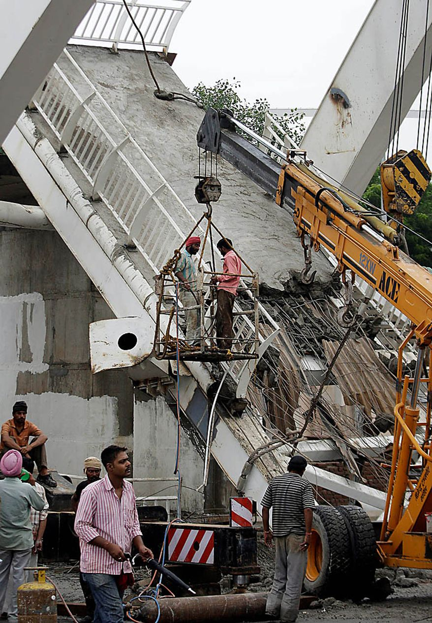 Workers clear the debris from a pedestrian bridge that collapsed Tuesday outside the Jawaharlal Nehru Stadium, the main venue for the Commonwealth Games, in New Delhi, India, Wednesday, Sept. 22, 2010. Top Indian officials dismissed international anger over the pedestrian bridge collapse and the revelation that sports officials arrived to find filth in the athlete's village, news reports said Tuesday. The statements come as some athletes announced they would not attend the Commonwealth Games, and international sports officials warned their countries may be forced to withdraw amid a frenzy of last-minute preparations. (AP Photo/Manish Swarup)