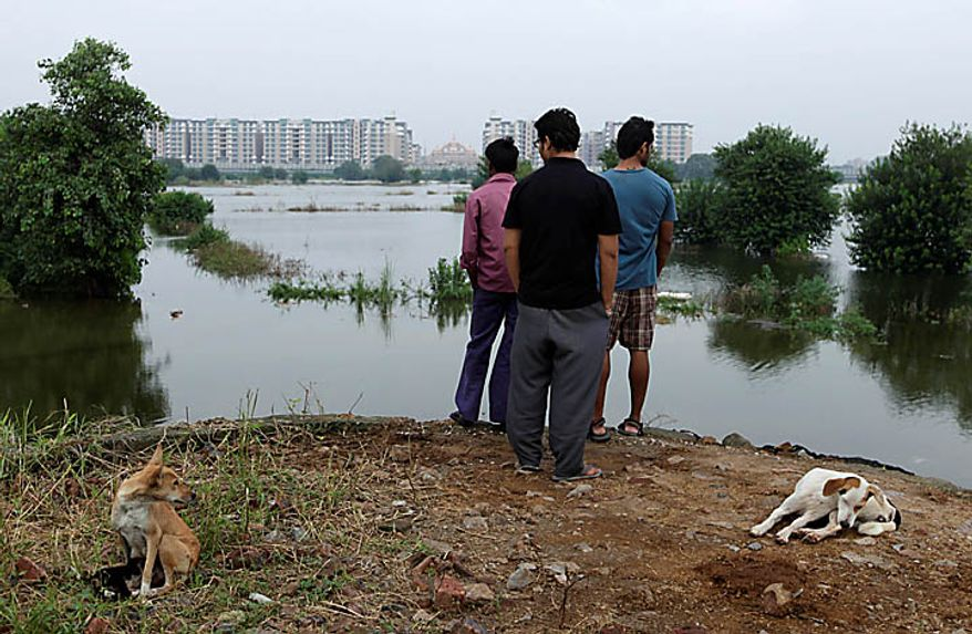 Locals look at the expanse of flood water that encircles the Commonwealth Games Village, background, in New Delhi, India, Wednesday, Sept. 22, 2010. Top Indian officials dismissed international anger over the pedestrian bridge collapse and the revelation that sports officials arrived to find filth in the athlete's village, news reports said Tuesday. The statements come as some athletes announced they would not attend the Commonwealth Games, and international sports officials warned their countries may be forced to withdraw amid a frenzy of last-minute preparations.   (AP Photo/Saurabh Das)