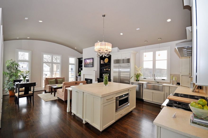 The center-island kitchen features white cabinets, limestone counters and stainless steel appliances.